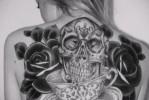 Тату черная роза на спине у девушке – рисунок с большим черепом
