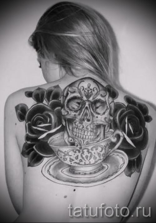 Тату черная роза на спине у девушке - рисунок с большим черепом