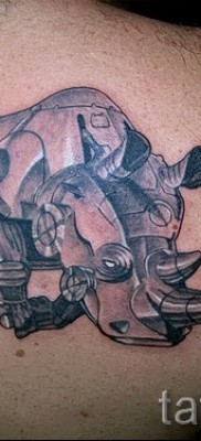 Фото пример тату носорог – носорог в металлических доспехах – выполнена на лопатке