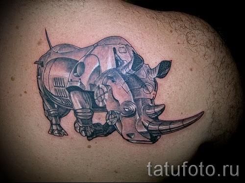 Фото пример тату носорог - носорог в металлических доспехах - выполнена на лопатке