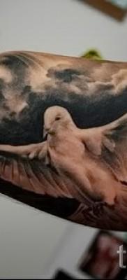 Фото тату голубь белого цвета в полете – небо в тучах – тату на руку для парня