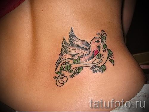 Фото тату голубь на боку (поясница) - выполнена на теле стройной девушки