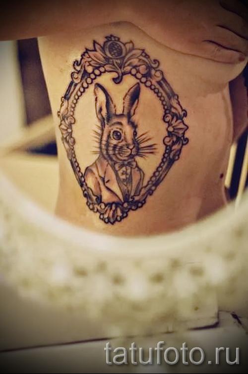Фото тату кролик в зеркале - работа на боку и ребрах у женщины