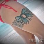 Фото тату подвязка с голубым бантом на бедре девушки в купальнике