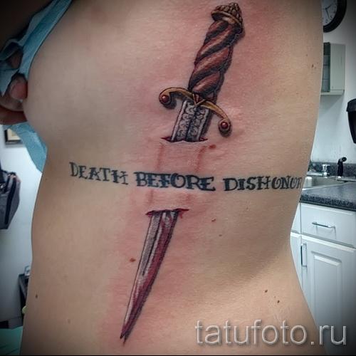 Тату нож в боку девушки и надписи