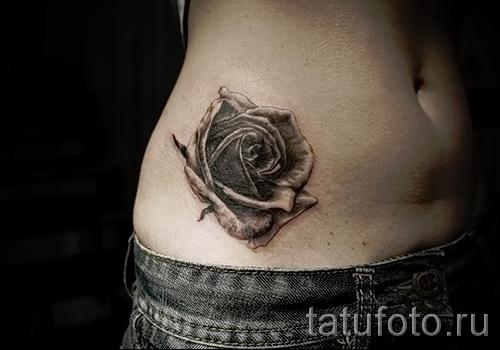 Тату черная роза на бедре - внизу живота у девушки