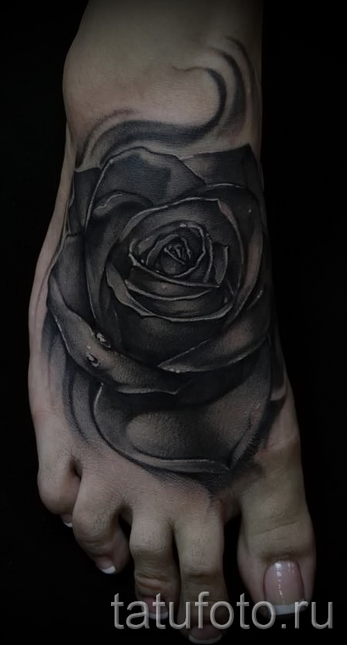 Тату черная роза на стопе у девушки