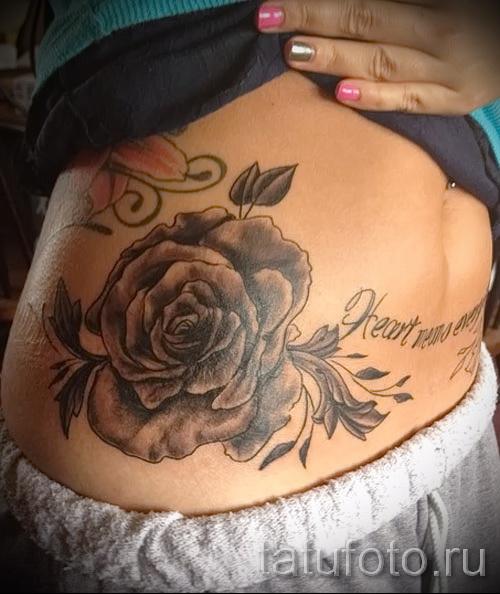 Тату черная роза с надписями внизу на животе
