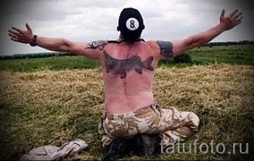 Фото тату щука - татуировка на спине у молодого мужчины-рыбака