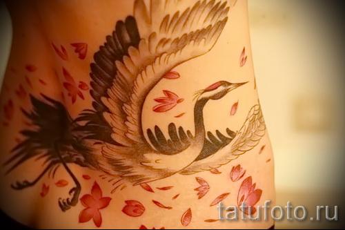 тату журавль фото пример - вариант с лепестками цветов - татуировка на пояснице у девушки