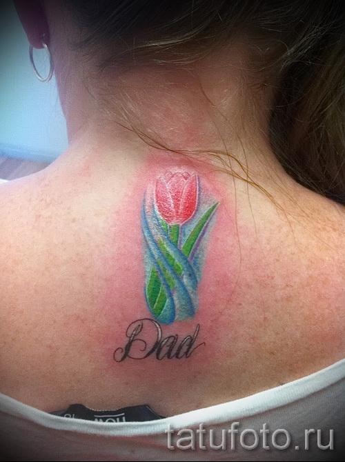 тату тюльпан фото - на спине у девушки с надписью (около шеи)