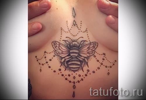 Пример тату пчелы на фото - вариант между грудей у молодой красивой девушки