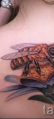 Пример тату пчелы на фото – пчела сидит на цветке – татуировка на спине у женщины