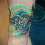 Фото готовой тату знак зодиака телец - зелено-желтая татуировка на запястье у мужчины