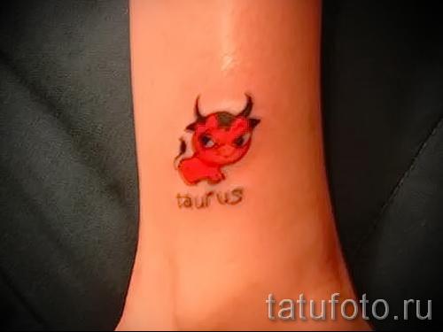 Фото готовой тату знак зодиака телец - маленький красный бычок и надпись