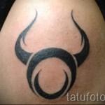 Фото готовой тату знак зодиака телец - простой символ на плече мужчины