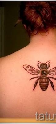 Фото тату пчела – по середине спины девушки