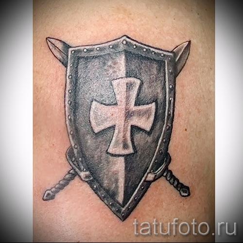 Фото тату щит с крестом и два перевернутых меча