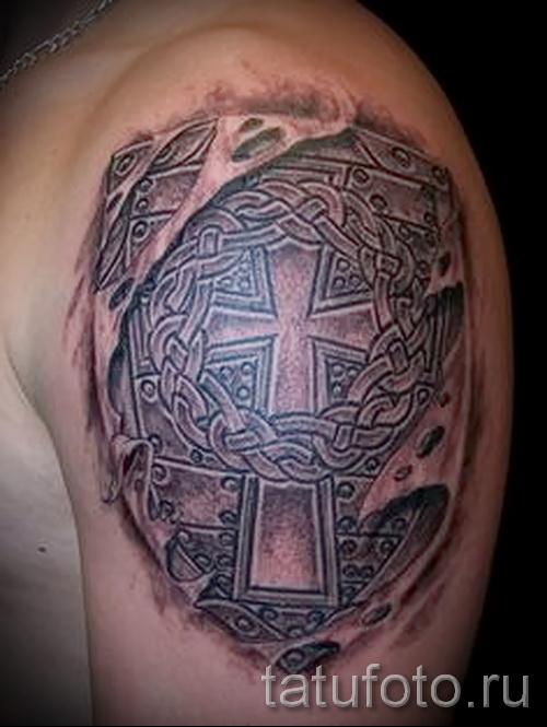 Фото тату щит с крестом - нанесена на плече у мужчины