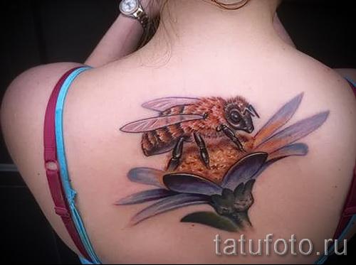 Пример тату пчелы на фото - пчела сидит на цветке - татуировка на спине у женщины