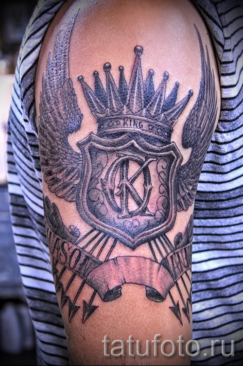 Фото тату щит - корона и стрелы - на плече парня