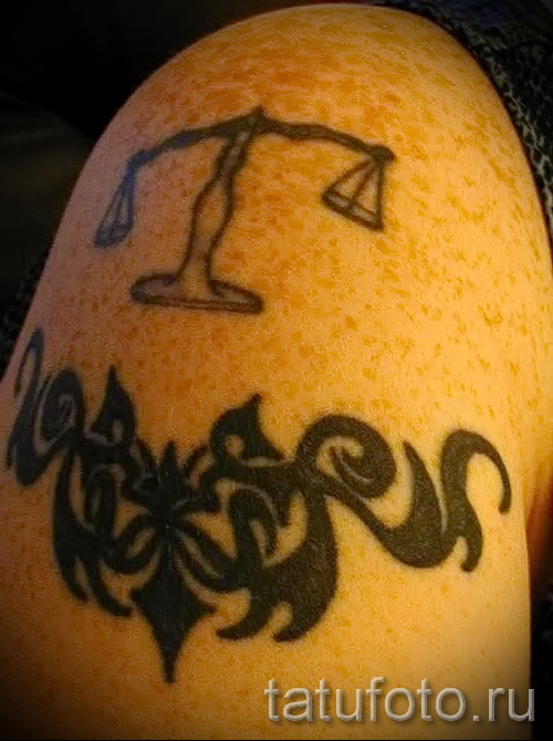 Libra tattoo on his arm - Photo example of the number 13122015 4
