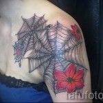 тату паутина на плече - вариант с красными цветами на теле девушки