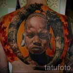 Фото тату портрет ребенка - цветная тату на всю с пину с лицом африканского ребенка и бивни животного