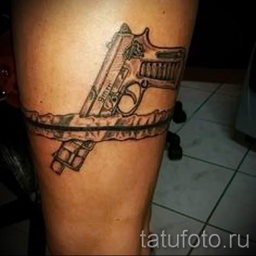 Jarretiere De Tatouage Avec Un Pistolet Photo Du Tatouage Fini
