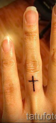 Фотография заслуживающей внимания уже нанесенной на тело тату на пальце с крестом для подбора и создания своего эскиза – пример