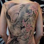 Крутой пример нанесенной тату журавль – рисунок подойдет для тату аист и цветы