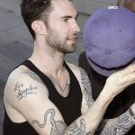 "Singer Adam Levine, a coach on ""The Voice"" bares his arms and his many tattoos outside the ""Jimmy Kimmel Live"" studios in Los Angeles"