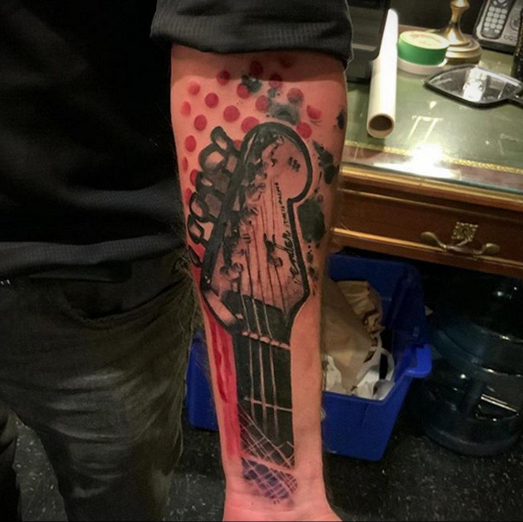 Черная тату с гитарным грифом на руку - фото