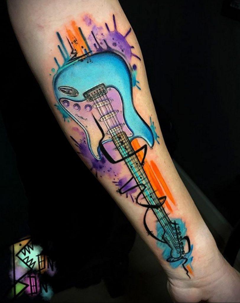 Яркая и цветная тату с гитарой и размытыми красками на руку - фото