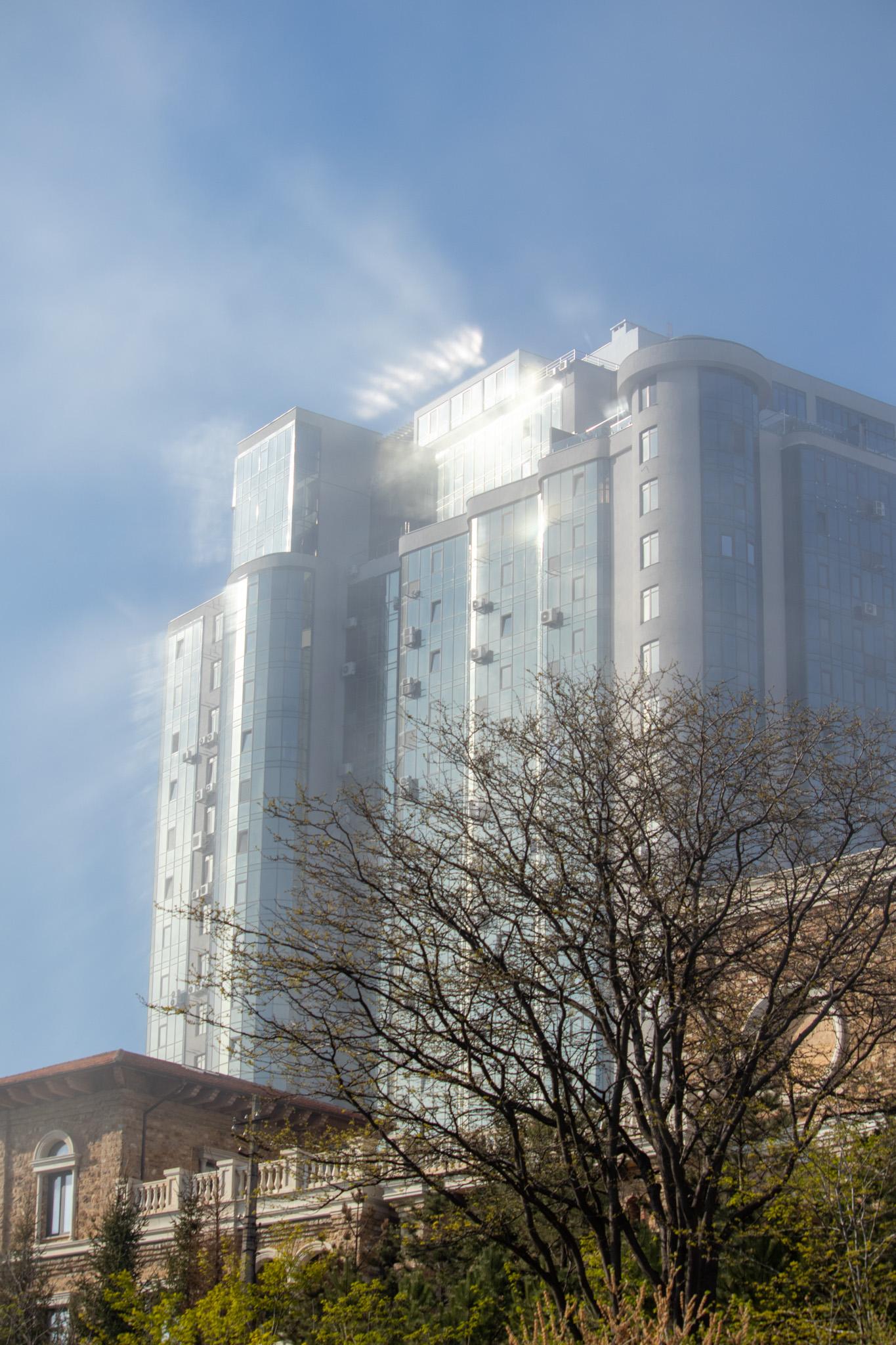 Остекленный фасад здания с бликами солнца в густом тумане 6