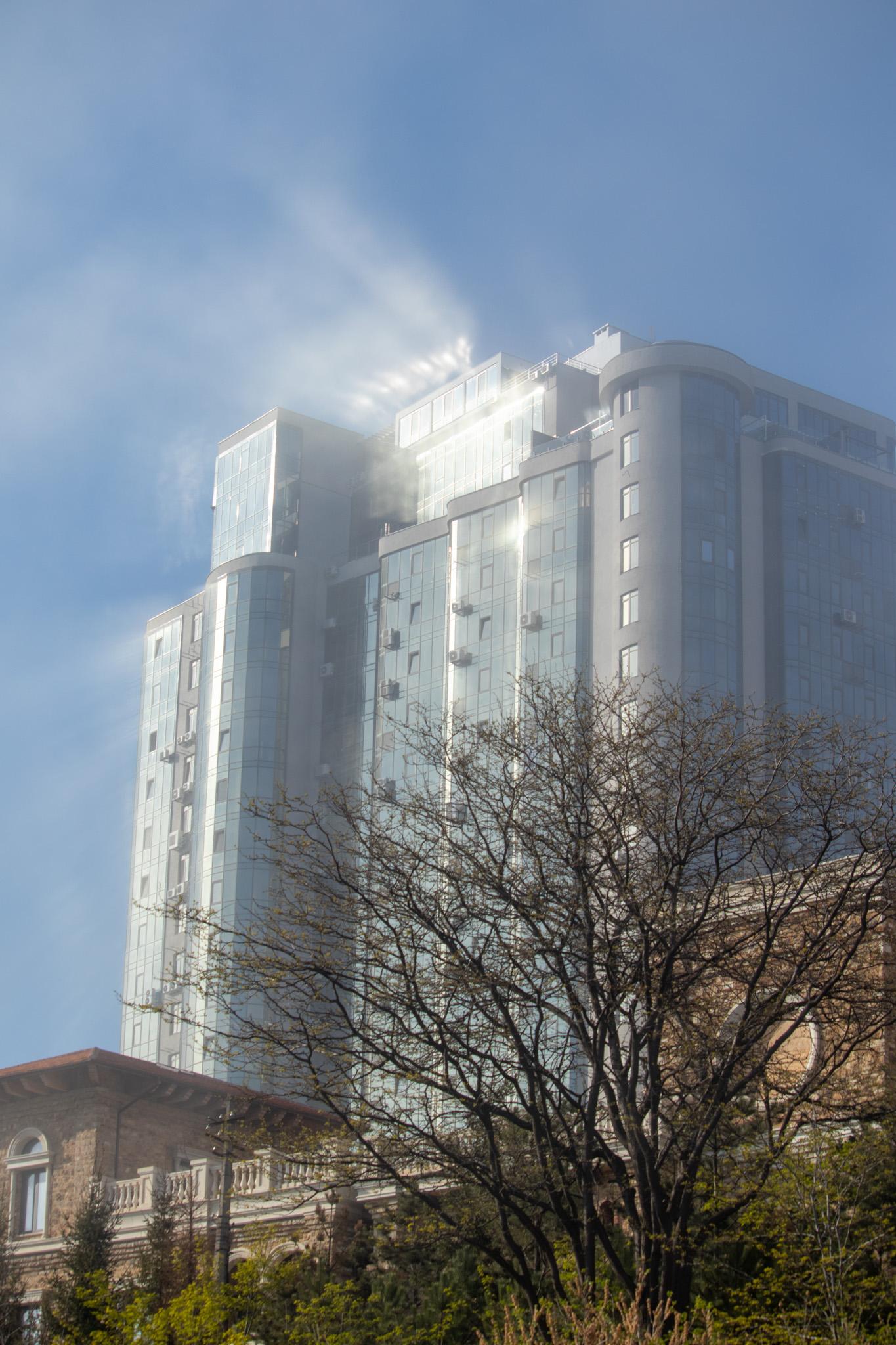 Остекленный фасад здания с бликами солнца в густом тумане 7