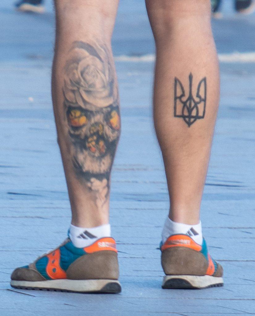 Фото тату на ногах парня с черепом и трезубцем – гербом Украины - Уличная татуировка (Street tattoo) 05052020 – tatufoto.com 2