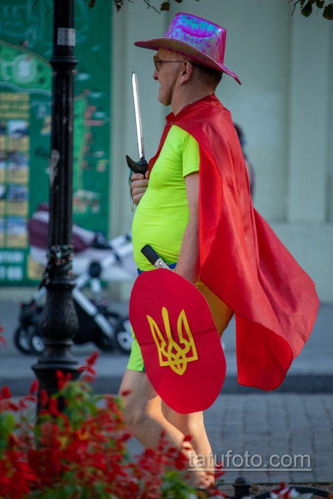 Фото мужчины в костюме героя с плащом и мечем – щитом с украинским гербом – Уличная татуировка 14.09.2020 – tatufoto.com 1