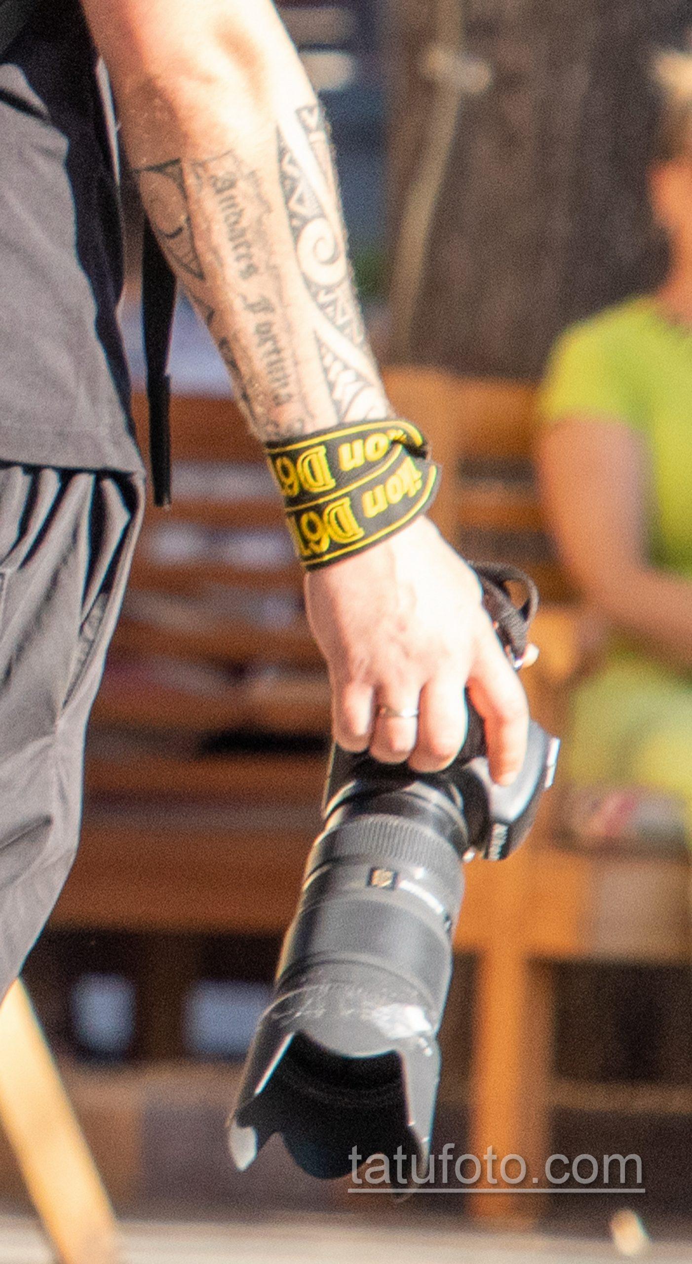 Фото тату с маори узорами и надписями на руке парня с фотоаппаратом Никон в руке девушки - Уличная татуировка 14.09.2020 – tatufoto.com 4