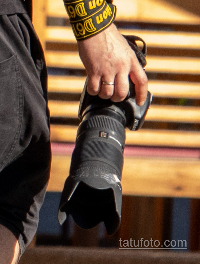 Фото тату с маори узорами и надписями на руке парня с фотоаппаратом Никон в руке девушки - Уличная татуировка 14.09.2020 – tatufoto.com 5