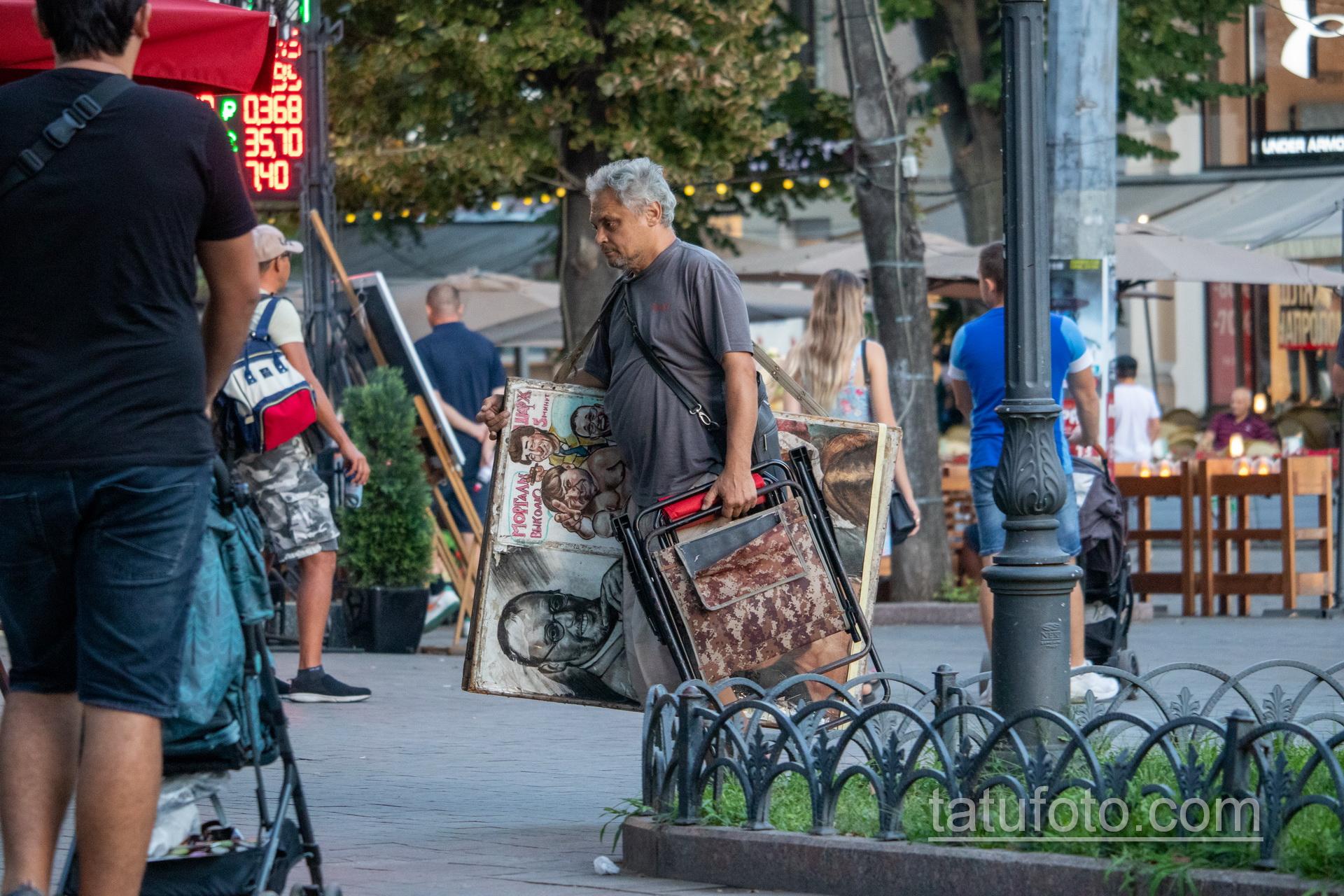 Фото уличного художника который несет картины и стул – Уличная татуировка 14.09.2020 – tatufoto.com 1