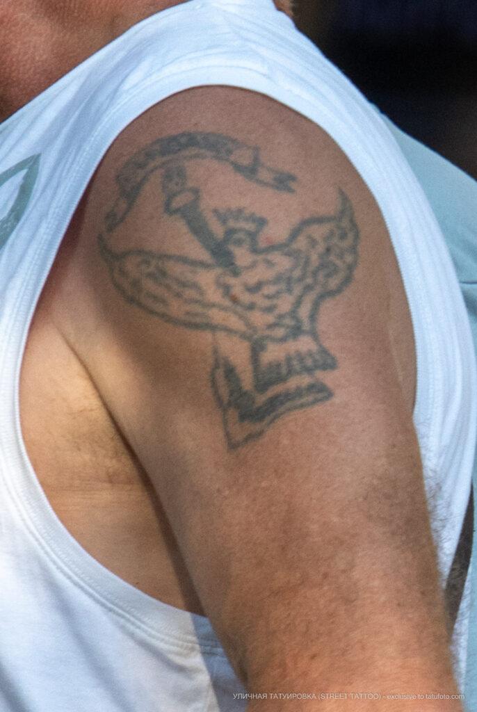Старая армейская тату с факелом, надписью и птицей на левом плече пожилого мужчины – Фото Уличная тату (street tattoo) № 13 – 27.06.2021 3